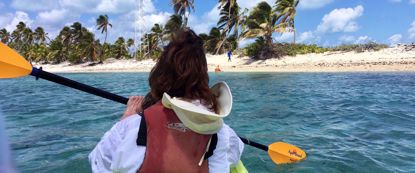 Woman kayaking through blue belize water