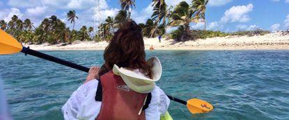 Woman kayaking through blue belize water