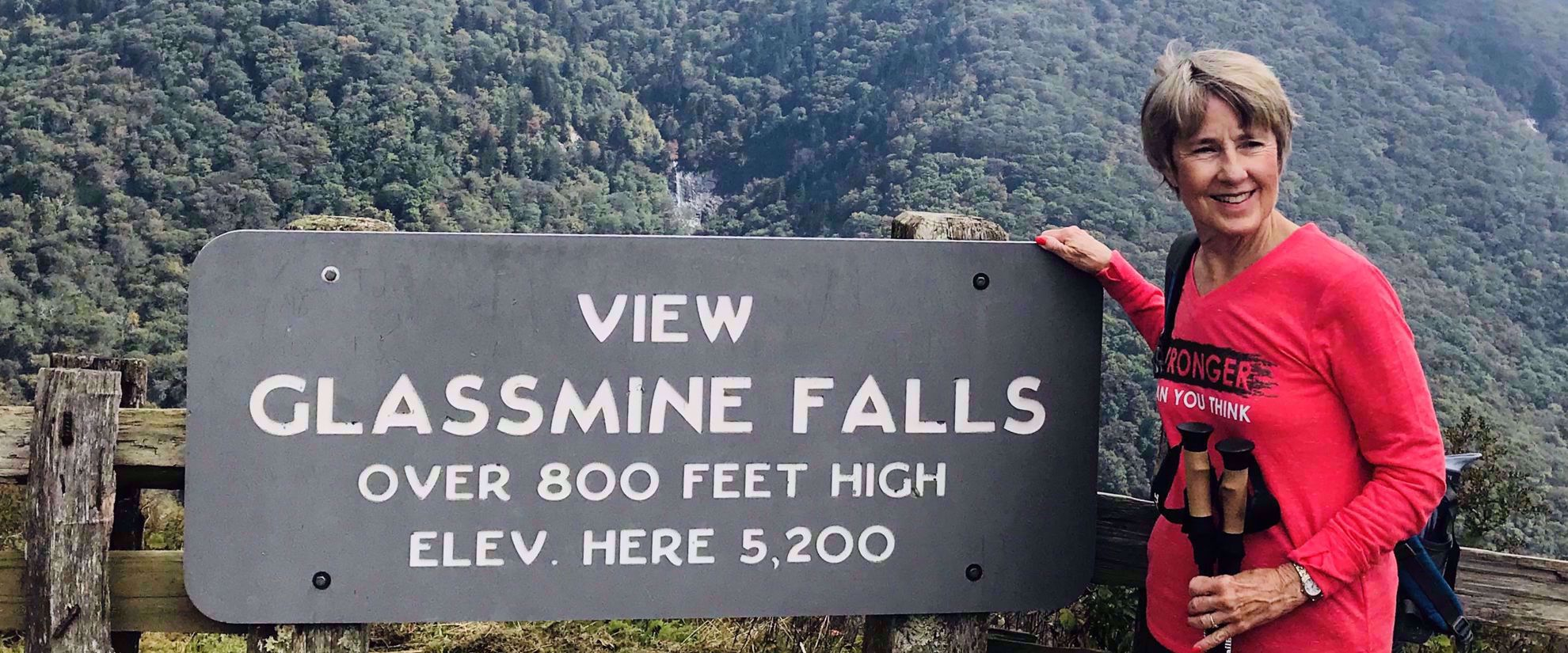 Woman smiling by Glassmine falls sign