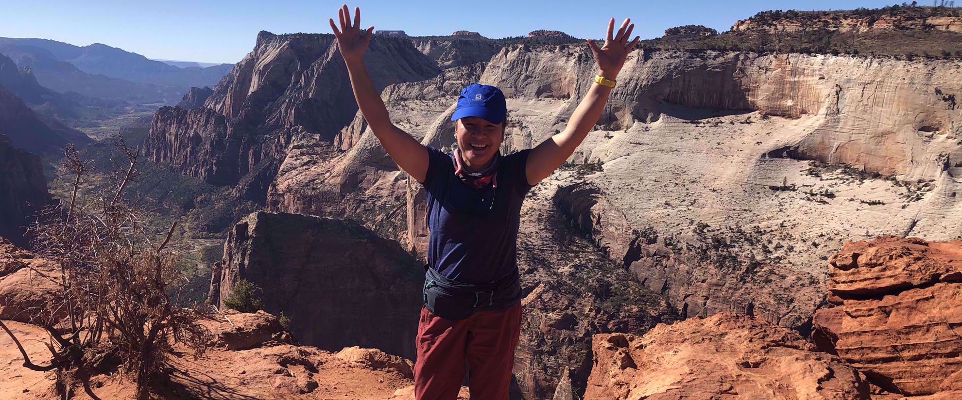 woman smiles after finishing hike in utah