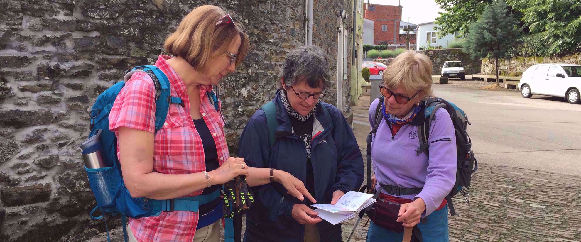 women studying trail map camino de santiago