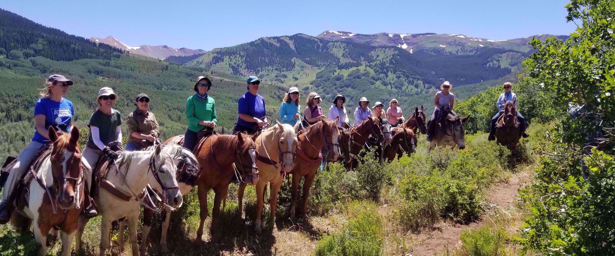women riding horsback through colorado rockies on adventure group tour