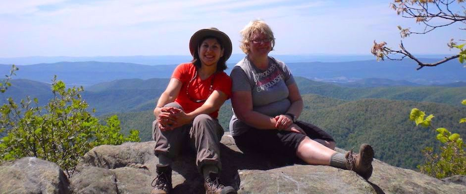 two women sitting smiling on rock appalachian trail