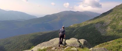 woman on rock enjoys view of valley on appalachian trail