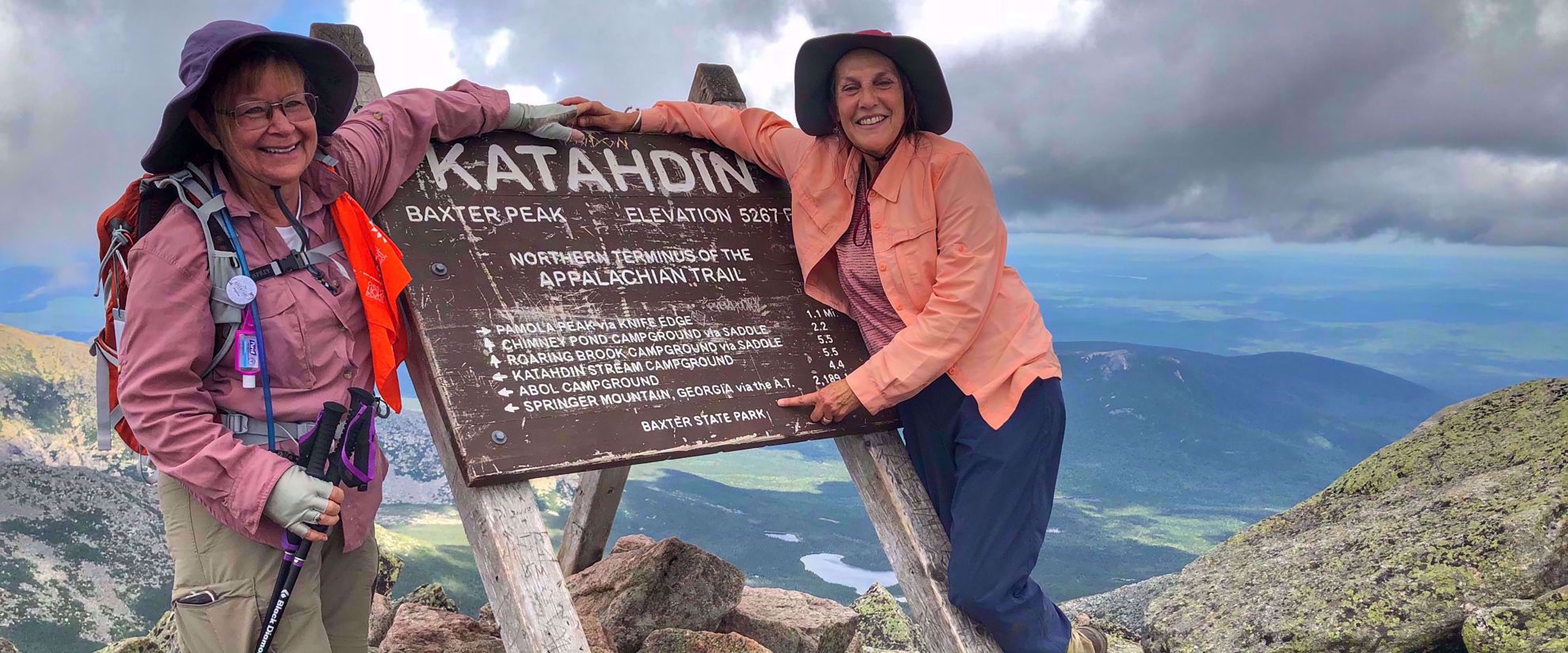 women smiling holding katahdin sign maine