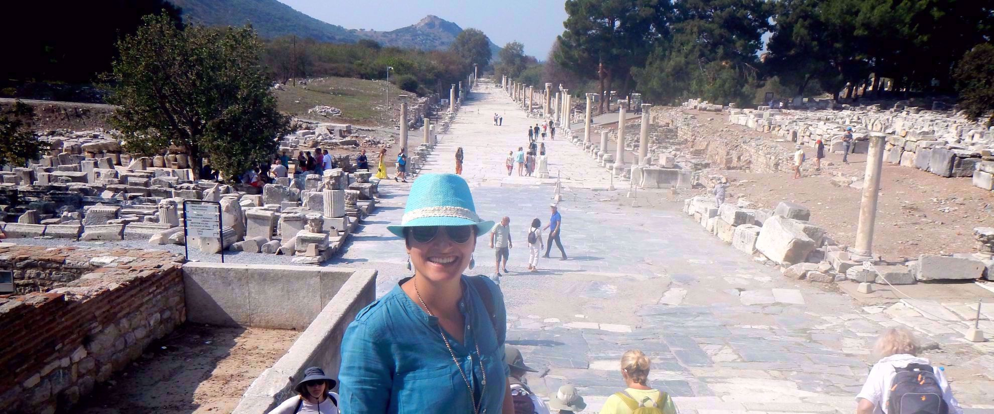 woman on group tour smiles for photo in turkish ruins