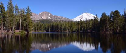 peaceful lake surrounded by pine trees with snow capped mountains