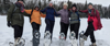 participants showing off their snowshoes on a dog sledding adventure trip in minnesota