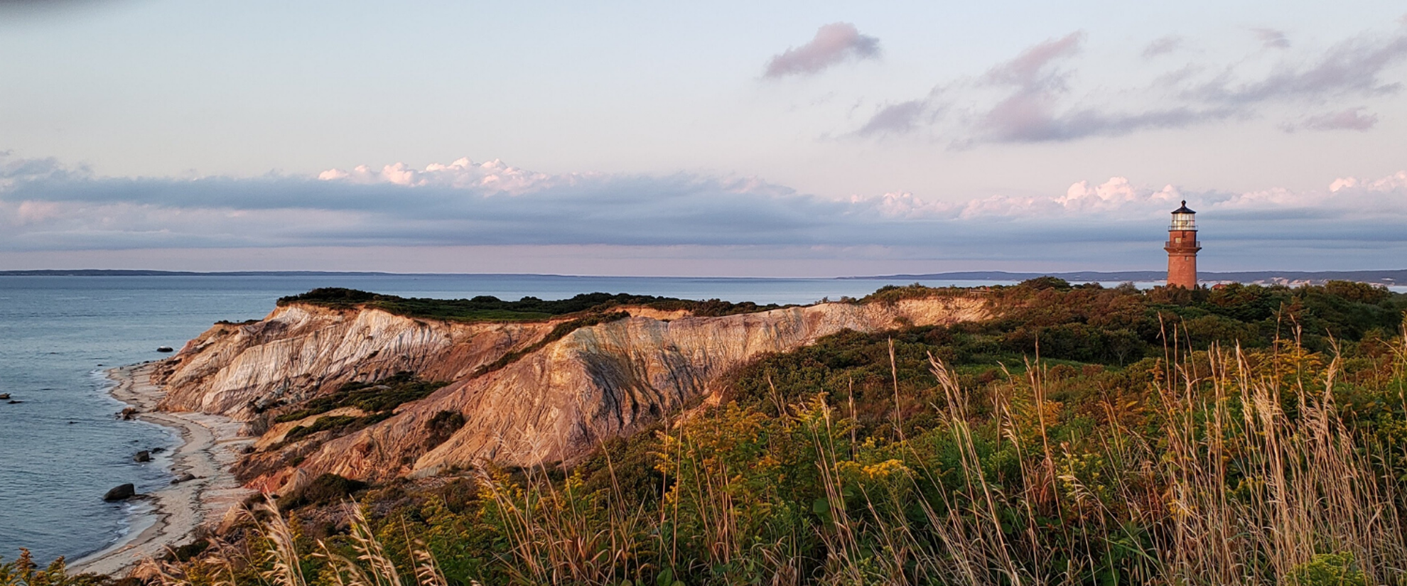 Classic lighthouse image. the sun is getting close to setting, but there is still some blue in the sky. there's a lovely hint of peach pastels on the horizon, craggy cliffs in the foreground
