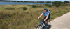 Cape cod is a perfect multisport adventure! This is a photo of  woman biking happily along the coast