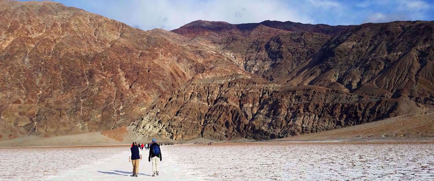 women hiking death valley rock formation